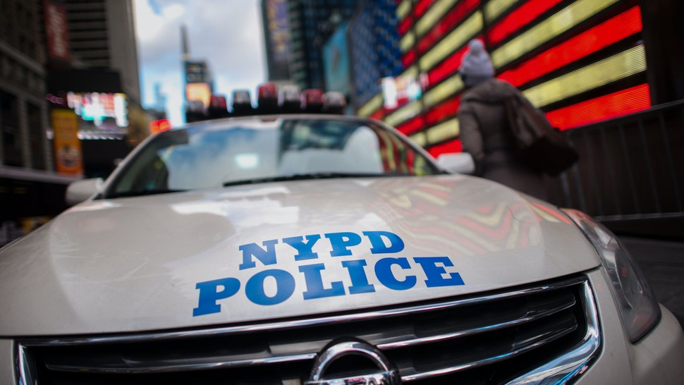 A pedestrians walks past a New York Police Department (NYPD) cruiser on patrol in the Times Square area of New York, U.S., on Monday, Jan. 5, 2015. The New York City Police Department redeployed officers in response to an attack at the Paris offices of a French weekly magazine, in what has become a regular step for the largest U.S. city following terrorist attacks in other parts of the world. Photographer: Craig Warga/Bloomberg via Getty Images