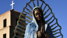 SANTA FE, NM - NOVEMBER 11, 2017: A bronze statue of Our Lady of Guadalupe stands beside the historic Santuario de Guadalupe in Santa Fe, New Mexico. Our Lady of Guadalupe (The Shrine of Our Lady of Guadalupe) was built in the 1770s. It is the oldest standing shrine in the United States. (Photo by Robert Alexander/Getty Images)