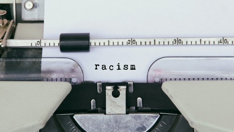 Racism Typed on Vintage Typewriter - stock photo