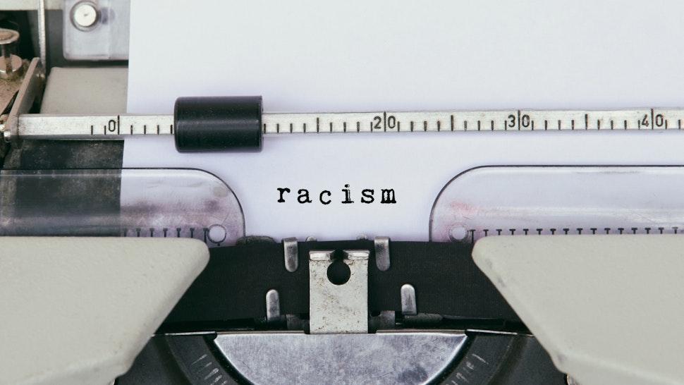 Racism Typed on Vintage Typewriter - stock photo
