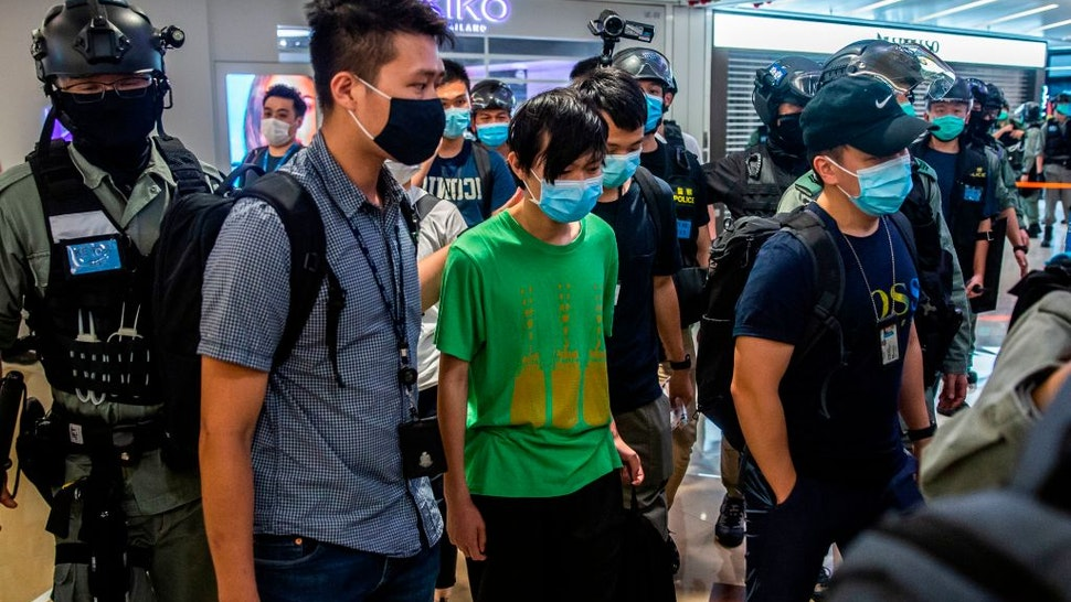 Police take away a man (C) during a demonstration in a mall in Hong Kong on July 6, 2020, in response to a new national security law introduced in the city which makes political views, slogans and signs advocating Hong Kongs independence or liberation illegal. - Hong Kongers are finding creative ways to voice dissent after Beijing blanketed the city in a new security law and police began making arrests for people displaying now forbidden political slogans. (Photo by ISAAC LAWRENCE / AFP) (Photo by ISAAC LAWRENCE/AFP via Getty Images)