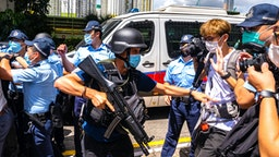 HONG KONG, CHINA - JULY 06: Police stand guard as defendant Tong Ying-kit, 23, arrives the court - Tong accused of deliberately driving his motorcycle into a group of police officers, is the first person charged for incitement to secession and terrorist activities under the national security law, on July 6, 2020 in Hong Kong, China.