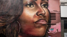 """A girl scoots past a mural of Michelle Obama in Brixton on June 24, 2020 in London, England. Yesterday, the Prime Minister Boris Johnson announced the reopening of restaurants, pubs, hairdressers and hotels on July 04 and the introduction of a """"one metre plus"""" social distancing rule. (Photo by Dan Kitwood/Getty Images)"""