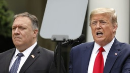 U.S. President Donald Trump speaks as Mike Pompeo, U.S. secretary of state, left, listens during a news conference in the Rose Garden of the White House in Washington, D.C., U.S., on Friday, May 29, 2020. Trump said the U.S. will terminate its relationship with the World Health Organization, which he has accused of being under Chinese control and failing to provide accurate information about the spread of coronavirus. Photographer: Yuri Gripas/Abaca/Bloomberg via Getty Images
