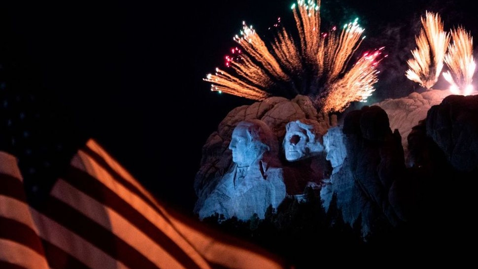 A US flag flies as fireworks explode above the Mount Rushmore National Monument during an Independence Day event attended by the US president in Keystone, South Dakota, July 3, 2020. (Photo by ANDREW CABALLERO-REYNOLDS / AFP)