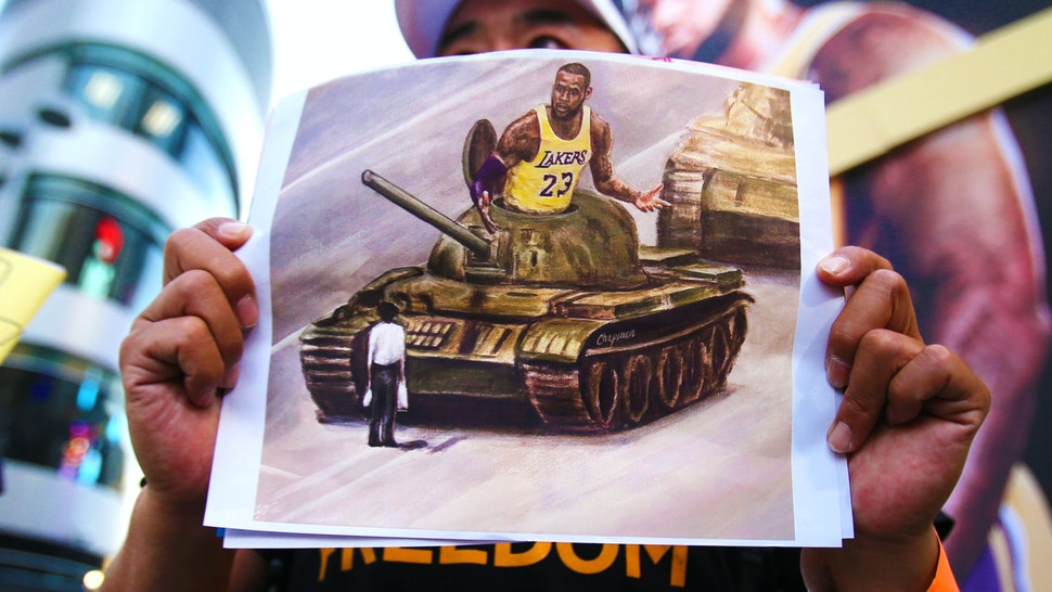 LOS ANGELES, CALIFORNIA - OCTOBER 22: A pro-Hong Kong activist holds an image depicting LeBron James aboard a Chinese tank in Tiananmen Square before the Los Angeles Lakers season opening game against the LA Clippers outside Staples Center on October 22, 2019 in Los Angeles, California. Activists also printed at least 10,000 pro-Hong Kong t-shirts to hand out to those attending the game and encouraged them to wear the free shirts as a form of peaceful protest against China amidst Chinese censorship of NBA games.