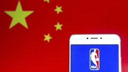 HONG KONG - 2019/04/06: In this photo illustration a American National Basketball Association (NBA) men's professional basketball league logo is seen on an Android mobile device with People's Republic of China flag in the background.