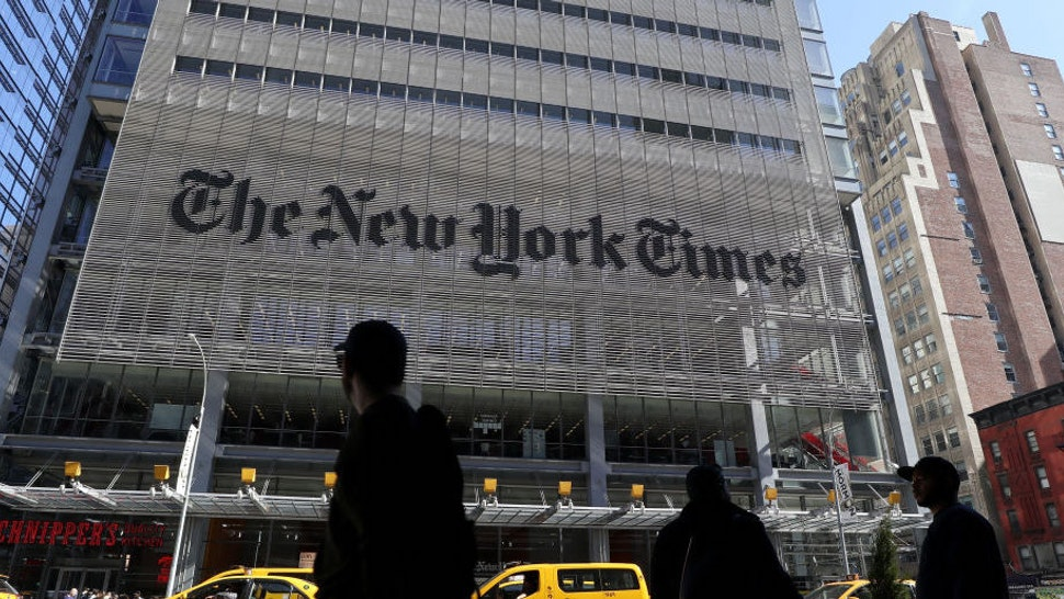 People walk along 8th Avenue in front of the New York Times headquarters on March 9, 2020 in New York City. (Photo by Gary Hershorn/Getty Images)