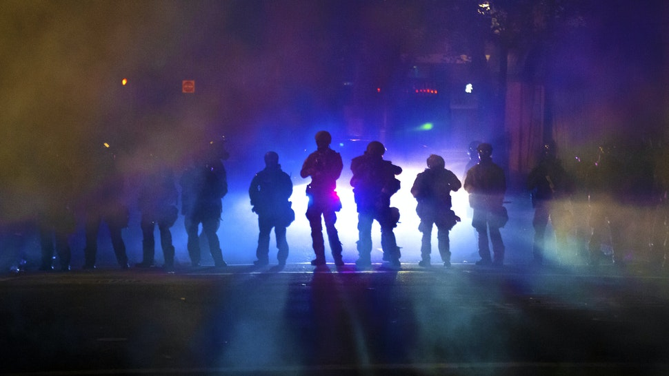 PORTLAND, OR - JULY 21: Federal officers walk through tear gas while dispersing a crowd of about a thousand people during a protest at Mark O. Hatfield U.S. Courthouse on July 21, 2020 in Portland, Oregon. State and city elected officials have called for the federal officers to leave Portland as clashes between protesters and federal police continue to escalate.