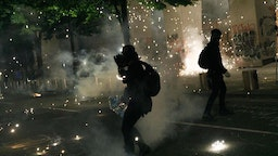 Tear gas and fireworks mix as Black Lives Matter supporters demonstrate in Portland, Oregon on July 4, 2020 for the thirty-eighth day in a row at Portland's Justice Center and throughout Portland, with a riot declared about 12.20 am on July 5. CS tear gas and less-lethal weapons were used, and multiple arrests were made. (Photo by John Rudoff/Anadolu Agency via Getty Images)