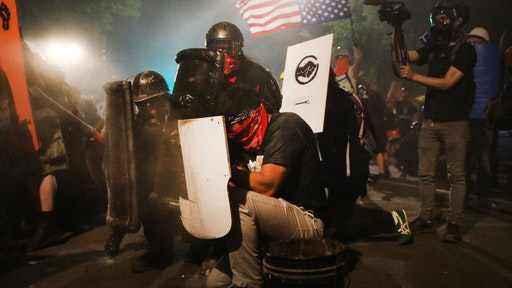 Protesters clash with federal police in front of the Mark O. Hatfield federal courthouse in downtown Portland as the city experiences another night of unrest on July 28, 2020 in Portland, Oregon. For over 57 straight nights, protesters in downtown Portland have faced off in often violent clashes with the Portland Police Bureau and, more recently, federal officers. The demonstrations began to honor the life of George Floyd and other black Americans killed by law enforcement and have intensified as the Trump administration called in the federal officers. (Photo by Spencer Platt/Getty Images)