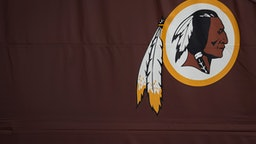 """LANDOVER, MD - JULY 07: A Washington Redskins logo is seen on the outside of FedEx Field on July 7, 2020 in Landover, Maryland. After receiving recent pressure from sponsors and retailers, the NFL franchise is considering a name change to replace Redskins. The term """"redskin"""" is a dictionary-defined racial slur for Native Americans."""