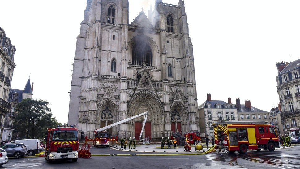 """Firefighters are at work to put out a fire at the Saint-Pierre-et-Saint-Paul cathedral in Nantes, western France, on July 18, 2020. - A blaze that broke inside the gothic cathedral of Nantes on July 18 has been contained, emergency officials said, adding that the damage was not comparable to last year's fire at Notre-Dame cathedral in Paris. """"The damage is concentrated on the organ, which seems to be completely destroyed. Its platform is very unstable and could collapse,"""" regional fire chief General Laurent Ferlay told a press briefing in front of the cathedral."""