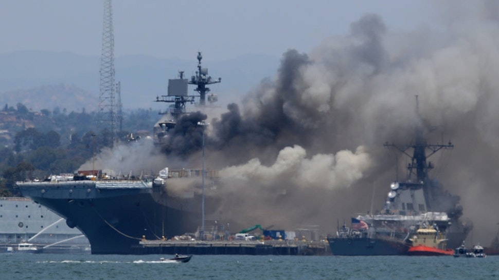 SAN DIEGO, CALIFORNIA - JULY 12: A fire burns on the amphibious assault ship USS Bonhomme Richard at Naval Base San Diego on July 12, 2020 in San Diego, California. There was an explosion on board the ship with multiple injuries reported.