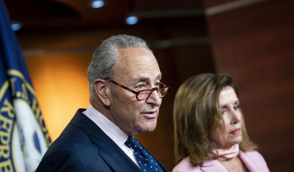 Lãnh đạo phe thiểu số Thượng viện Chuck Schumer, một đảng viên Dân chủ từ New York, phát biểu khi Chủ tịch Hạ viện Hoa Kỳ Nancy Pelosi, một đảng viên đảng Dân chủ từ California, phải, lắng nghe trong một cuộc họp báo tại Điện Capitol Hoa Kỳ ở Washington,