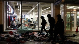 People walk past a store thats been looted during a riot following a peaceful rally expressing outrage over the death of George Floyd on May 30, 2020 in Seattle, Washington. Protests have erupted nationwide after Floyd died while in the custody of police in Minneapolis. (Photo by Karen Ducey/Getty Images)