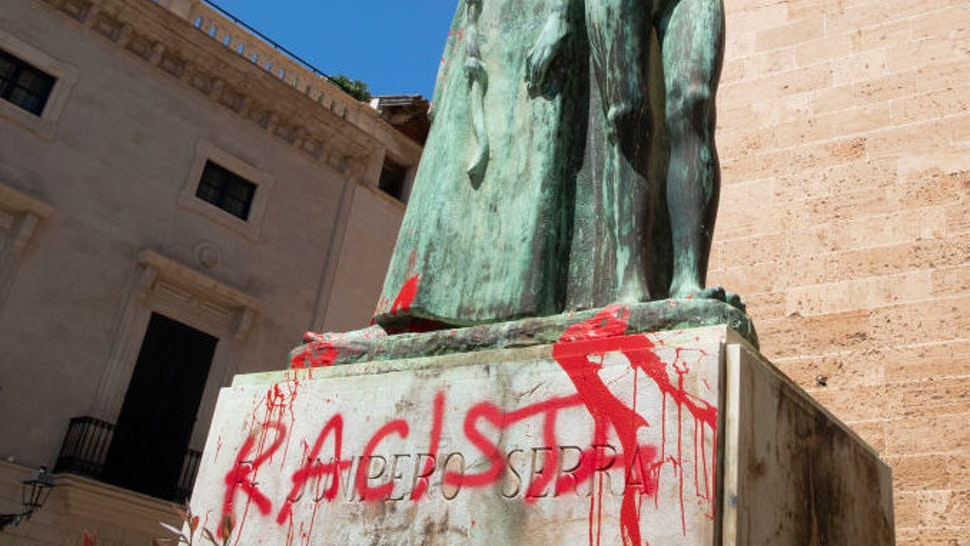 """The statue of the Roman Catholic Spanish priest Junipero Serra is pictured in Palma de Mallorca on June 22, 2020, after it was daubed with graffiti reading """"Racist"""". - The protests against racial inequality and police brutality have seen the toppling or removal of statues depicting Confederate generals, colonial figures and slave traders in the United States, Britain and New Zealand. (Photo by JAIME REINA / AFP) (Photo by JAIME REINA/AFP via Getty Images)"""