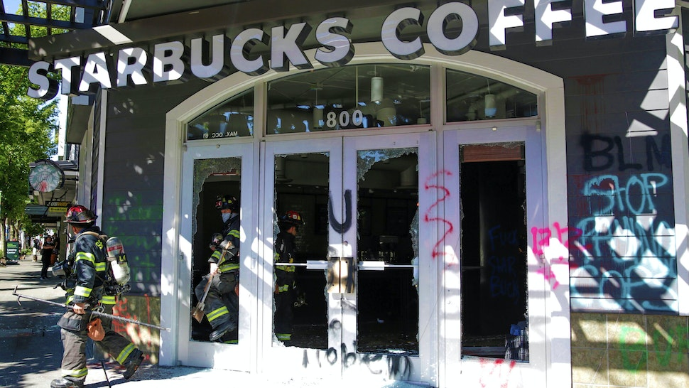 """Firefighters exit a Starbucks Coffee that was vandalized by protesters during demonstrations over Special Response Team presence in Seattle, Washington on July 25, 2020. - Police in Seattle used flashbang grenades and pepper spray Saturday against protesters who set fire to construction trailers outside a youth jail, amid a wave of public anger over President Donald Trump's planned """"surge"""" of federal agents into major cities."""