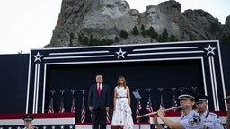 U.S. President Donald Trump, left, and First Lady Melania Trump attend an event at Mount Rushmore National Memorial in Keystone, South Dakota, U.S., on Friday, July 3, 2020. The early Independence Day celebration, which will feature a military flyover and the first fireworks in more than a decade, is expected to include about 7,500 ticketed guests who won't be required to wear masks or socially distance despite a spike in U.S. coronavirus cases.
