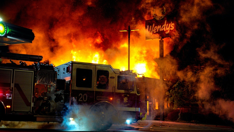 ATLANTA, USA - JUNE 13: Demonstrators set on fire a restaurant during the protest after an Atlanta police officer shot and killed Rayshard Brooks, 27, at a Wendy's fast food restaurant drive-thru Friday night in Atlanta, United States on June 13, 2020. As nationwide protests slowed in the death of George Floyd, anger again erupted Saturday in the US over the fatal shooting of another black man. Mayor Keisha Lance Bottoms announced Atlanta Police Chief Ericka Shields voluntarily stepped down from the department earlier in the day.