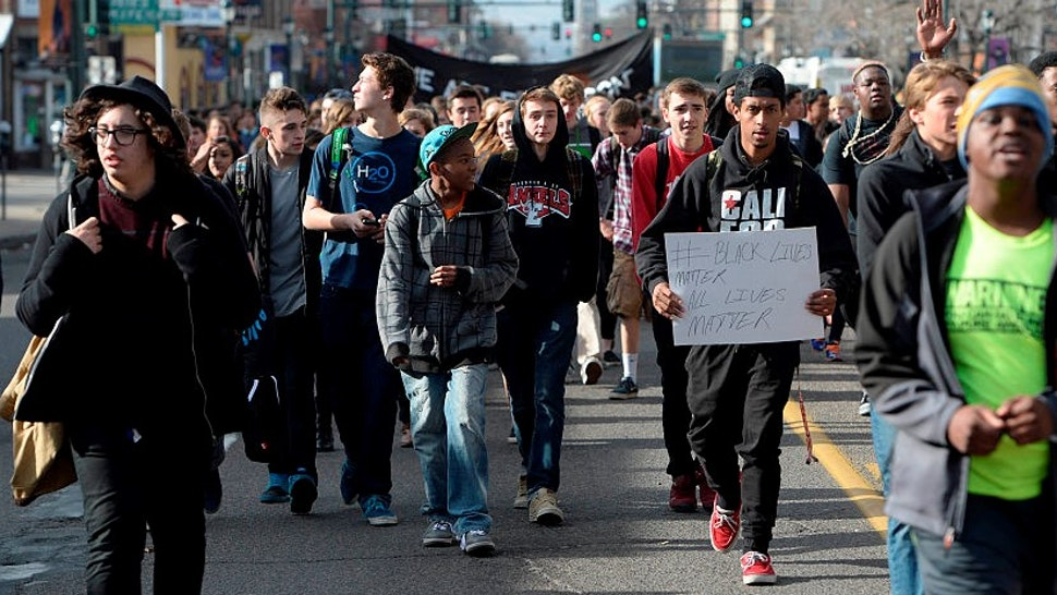 DENVER, CO - DECEMBER 03: East High School students gather and sit in the intersection of York St and Colfax Ave during a Ferguson walkout and protest only a few block east of where four Denver Police officers on bicycles were hit by a vehicle traveling west on Colfax. All of the officers were transported to Denver Health Medical center December 03, 2014 with unknown conditions. (Photo b