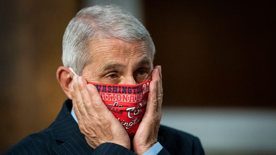 WASHINGTON, DC - JUNE 30: Anthony Fauci, director of the National Institute of Allergy and Infectious Diseases, adjusts a Washington Nationals protective mask while arriving to a Senate Health, Education, Labor and Pensions Committee hearing on June 30, 2020 in Washington, DC. Top federal health officials are expected to discuss efforts to get back to work and school during the coronavirus pandemic. (Photo by
