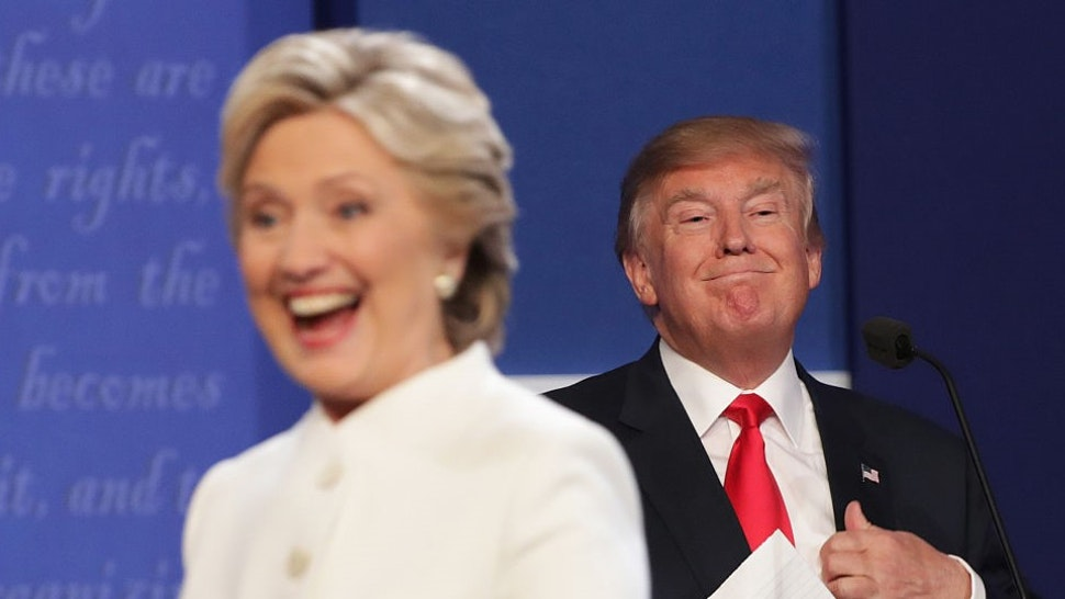 LAS VEGAS, NV - OCTOBER 19: Democratic presidential nominee former Secretary of State Hillary Clinton walks off stage as Republican presidential nominee Donald Trump smiles after the third U.S. presidential debate at the Thomas & Mack Center on October 19, 2016 in Las Vegas, Nevada. Tonight is the final debate ahead of Election Day on November 8. (Photo by