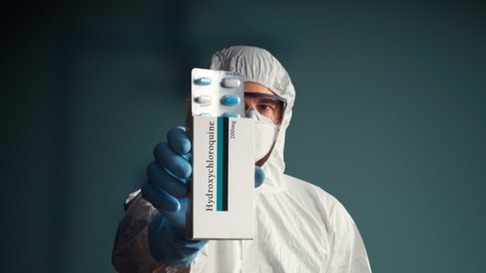Medical worker in full protective suit holding hydroxychloroquine drug tablets