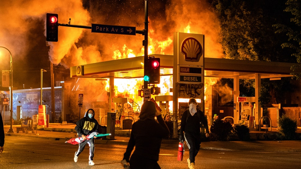 MINNEAPOLIS, MN - MAY 29: Protesters walk past a gas station on the corner of Park Ave S and E. Lake St that is on fire on Friday, May 29, 2020, in Minneapolis, MN. Protests in the wake of the death of George Floyd while in police custody swept country overnight Thursday.