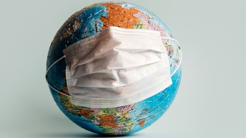 Globe made of jigsaw puzzles with a protective medical mask as a prophylaxis in the fight against coronavirus infection. Measures against the spread of the virus