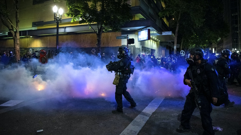 Federal law enforcement throw tear gas at the crowd of demonstrators during a night of protest against racial injustice police brutality and the deployment of federal troops to US cities on July 29, 2020 in Portland, Oregon. - Protests in the US city of Portland have continued for more than 60 days. President Donald Trump's administration on July 29 agreed to a deal to defuse weeks of clashes with the withdrawal of federal forces whose presence enraged protesters, but the timing remained in dispute.