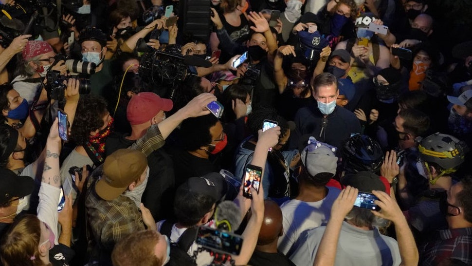 Portland Mayor Ted Wheeler speaks to the media while surrounded by press and protesters in front of the Multnomah County Justice Center on July 22, 2020 in Portland, Oregon. Mayor Wheeler made an appearance Wednesday at the ongoing protests in Portland despite being a popular topic of scorn among protesters. (Photo by