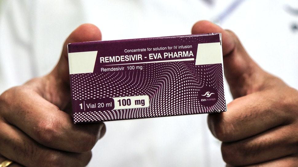 29 June 2020, Egypt, Giza: An employee of Egyptian pharmaceutical company Eva Pharma holds a pack containing vials of Remdesivir, a broad-spectrum antiviral medication approved as a specific treatment for COVID-19, at the company's factory, which started producing the drug this week with a production capacity of up to 1.5 million doses per month.