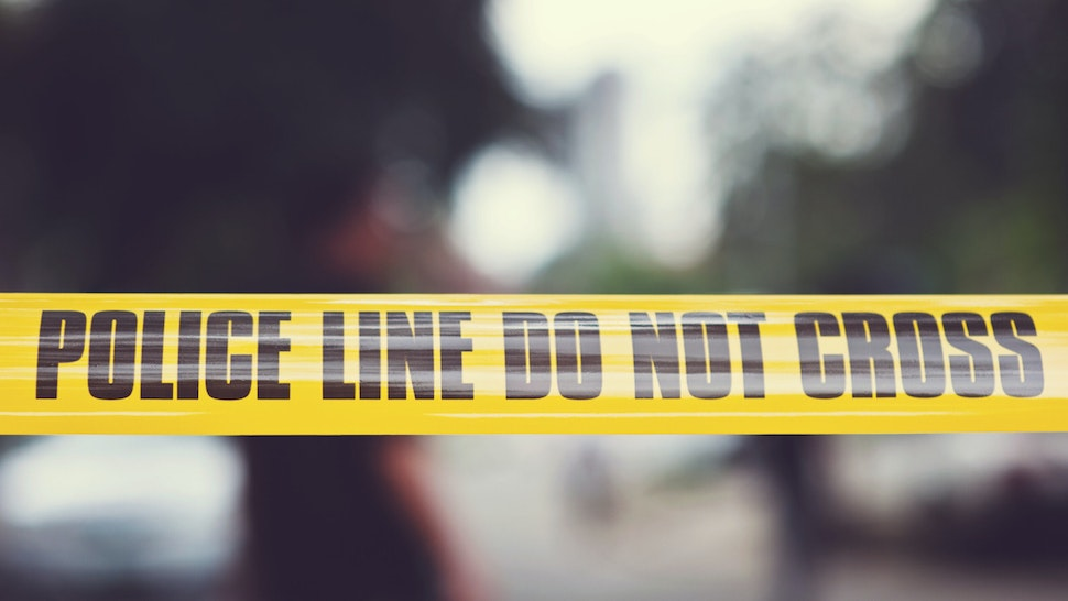 """Yellow police tape says """"police line do not cross"""" is set against blurry background."""