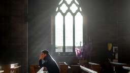 A man prays in a church as shoppers make their last minute purchases on Christmas Eve on December 24, 2018 in Birmingham, England.