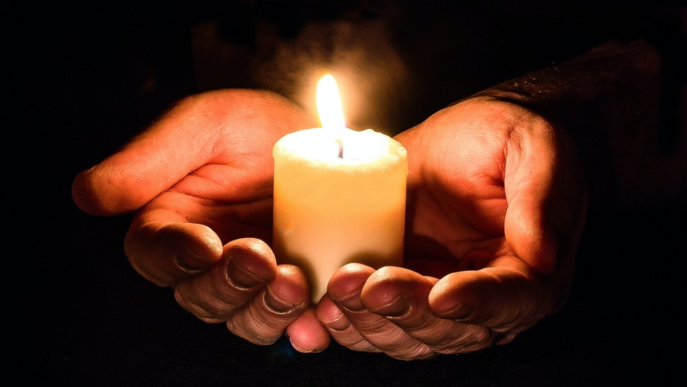 Cropped Hands Holding Illuminated Candle Against Black Background - stock photo.