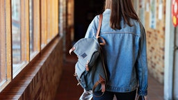 Rear view of young woman with backpack walking in corridor at university.