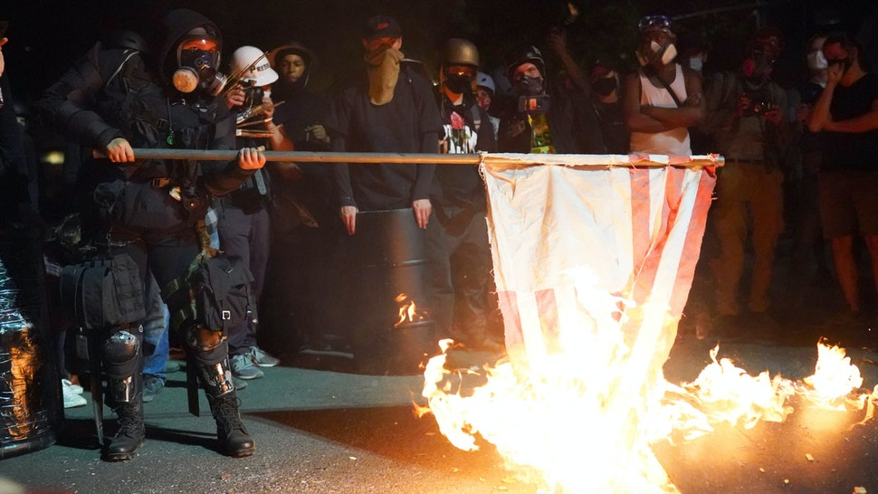 A protester burns an American flag in front of the Mark O. Hatfield U.S. Courthouse in the early morning on August 1, 2020 in Portland, Oregon. Friday was the second night in a row without police intervention, following weeks of clashes between federal officers and protesters in Portland.