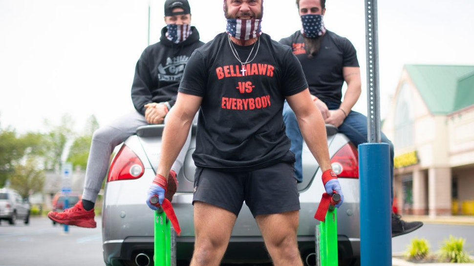 BELLMAWR, NJ - MAY 20: A body builder lifts a car and two men in the parking lot outside the Atilis Gym on May 20, 2020 in Bellmawr, New Jersey. The gym has opened for the third consecutive day, defying the New Jersey Governor's mandate that many retail businesses stay closed due to the coronavirus pandemic. (Photo by Mark Makela/Getty Images)