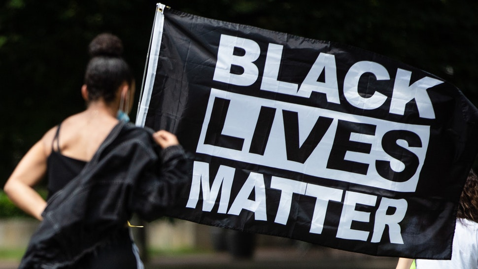 "27 June 2020, Baden-Wuerttemberg, Stuttgart: ""Black Lives Matter"" stands in the city garden on the flag of a participant in a demonstration against racism."