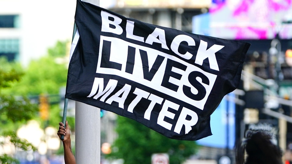 ATLANTA, GA - MAY 29: A man waves a Black Lives Matter flag during a protest on May 29, 2020 in Atlanta, Georgia. Demonstrations are being held across the US after George Floyd died in police custody on May 25th in Minneapolis, Minnesota.