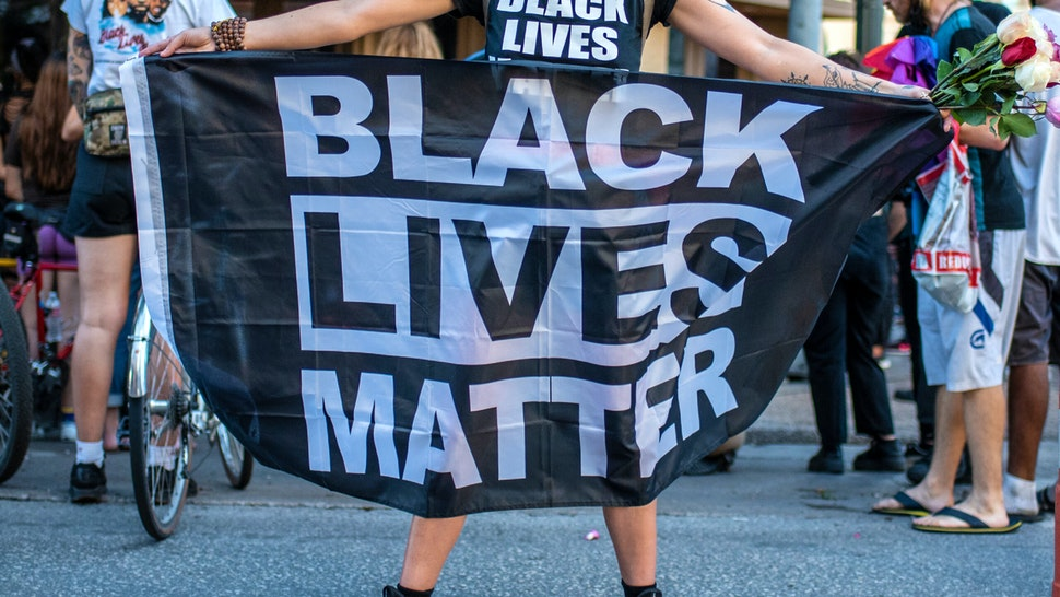 """AUSTIN, TX - JULY 26: A person holds up a """"Black Lives Matter"""" banner at a vigil for Garrett Foster on July 26, 2020 in downtown Austin, Texas. Garrett Foster, 28, who was armed and participating in a Black Lives Matter protest, was shot and killed after a chaotic altercation with a motorist who allegedly drove into the crowd. The suspect, who has yet to be identified, was taken into custody."""