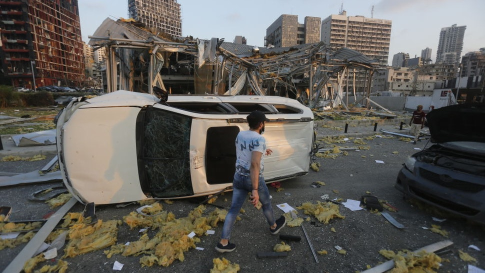BEIRUT, LEBANON - AUGUST 04: A man walks by an overturned car and destroyed buildings on August 4, 2020 in Beirut, Lebanon. At least 50 people were killed and thousands more injured when two explosions occurred near the Lebanese capital's port area.