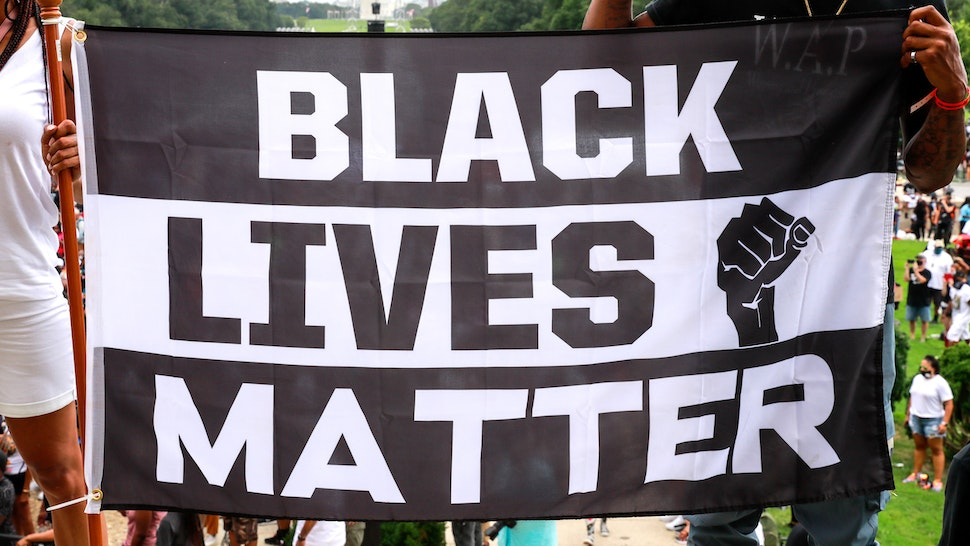 WASHINGTON, DC - AUGUST 28: Protesters hold a sign in support of Black Lives Matter during the Commitment March on August 28, 2020 in Washington, DC. Rev. Al Sharpton and the National Action Network organized a march with families who lost loved ones to police brutality, calling for criminal justice reform and demanding changes to federal legislation against police misconduct. Today would mark the 57th anniversary of Martin Luther King Jr.'s March on Washington.