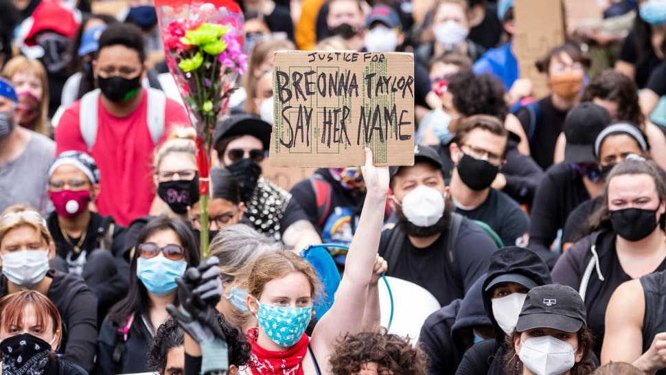 """A white protester wearing a mask holds a sign that says, """"Justice for Breonna Taylor Say Her Name"""" while another protester holds a bouquet of flowers next to them among the large crowd in Foley Square. On July 30, 2020, Oprah Magazine announced that they were going to feature Breonna Taylor on the cover. This is the first time someone other than Oprah has been on the cover of Oprah Magazine in its 20 year history. On July 28, 2020 Nikki Stone a homeless transgender woman was abducted off the streets and taken onto an unmarked van and arrested. Protesters took to the streets across America after the killing of George Floyd at the hands of a white police officer Derek Chauvin that was kneeling on his neck during his arrest as he pleaded that he couldn't breathe. The protest are attempting to give a voice to the need for human rights for African American's and to stop police brutality against people of color. Many people were wearing masks and observing social distancing due to the coronavirus pandemic. Leaders of the protest were clear that they wanted it to be a peaceful protest in light of nights of unrest looting and destruction. Photographed in the Manhattan Borough of New York on June 02, 2020, USA. (Photo by Ira L. Black/Corbis via Getty Images)"""