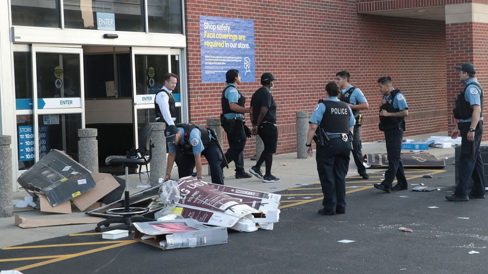 CHICAGO, ILLINOIS - AUGUST 10: Police officers detain a man who was found inside of a Best Buy store after parts of the city had widespread looting and vandalism, on August 10, 2020 in Chicago, Illinois. Police made several arrests during the night of unrest and recovered at least one firearm. (Photo by Scott Olson/Getty Images)