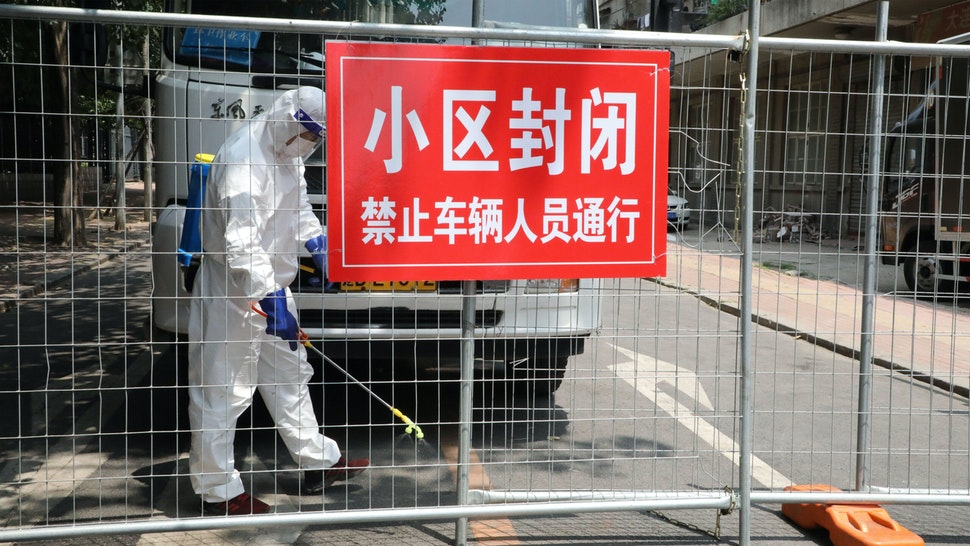 A worker wearing a protective suit sprays disinfectant at a closed residential community on July 29, 2020 in Dalian, Liaoning Province of China.