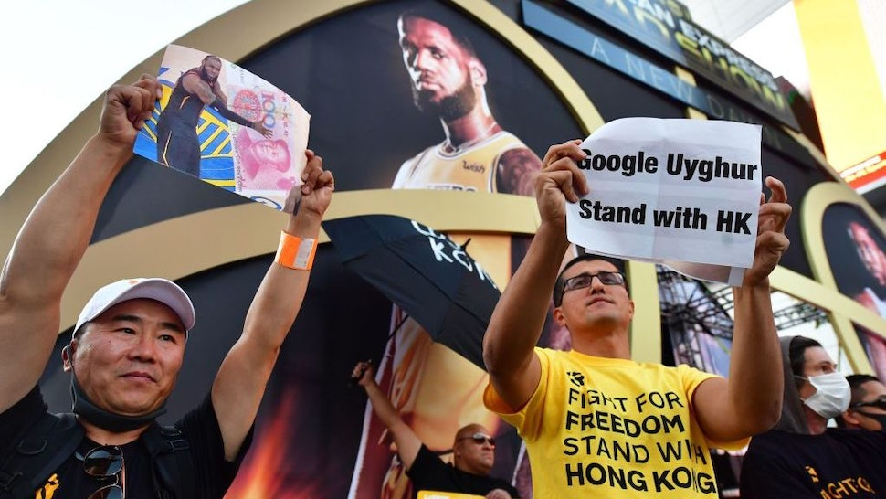 """Anti-Chinese Communist Party activists protest outside Staples Center ahead of the Lakers vs Clippers NBA season opener in Los Angeles on October 22, 2019. - Activists handed out free T-shirts displaying support for the Hong Kong protests after an NBA fan in Northern California raised enough money to pay for more than 10,000 shirts, according to the organizer who goes by the pseudonym """"Sun Lared"""" as LeBron James of the Lakers suffers the brunt of people's anger after comments he made in response to the tweet from Houston Rockets GM Daryl Morey in support of Hong Kong protesters, and drawing the ire of the Chinese Communist Party. (Photo by Frederic J. BROWN / AFP)"""