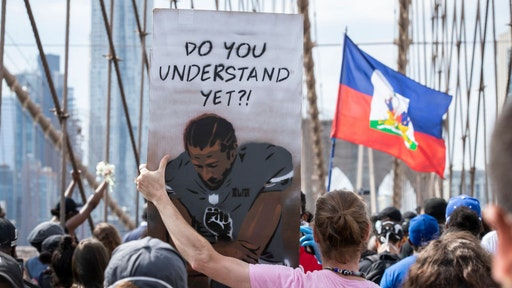 "A Caucasian protester holds a sign that says,""Do You Understand Yet?"" with a picture of Colin Kaepernick, former quarterback for the San Francisco 49ers, taking a knee with a Black Power Fist on in the middle of his jersey with the Arches of the Brooklyn Bridge behind them as they walk across the Brooklyn Bridge in protest of police racism. Protesters walked from Brooklyn to Manhattan after a memorial ceremony in Brooklyn with Terrence Floyd, brother of George Floyd. Protesters have taken to the streets across America and around the world after the killing of George Floyd at the hands of a white police officer Derek Chauvin that was kneeling on his neck during his arrest as he pleaded that he couldn't breathe. The protest are attempting to give a voice to the need for human rights for African American's and to stop police brutality against people of color. Many people were wearing masks and observing social distancing due to the coronavirus pandemic. Terrence Floyd echoed the word of peaceful protest saying that violent protests are overshadowing What's Going On. New York City remains in a curfew as an answer to nights of unrest looting and destruction. Photographed in the Manhattan Borough of New York on June 04, 2020, USA. (Photo by Ira L. Black/Corbis via Getty Images)"