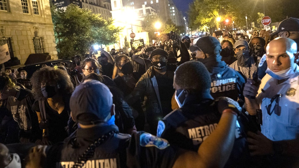 Protesters wearing protective masks stand at a police line at a demonstration on Black Lives Matter Plaza during the Republican National Convention in Washington, D.C., U.S., on Thursday, Aug. 27, 2020. President Trump will ask Americans to return him to office in a speech closing the convention, arguing that voters can't trust Joe Biden or the Democratic Party to navigate the coronavirus pandemic or salve the nation's racial divisions.